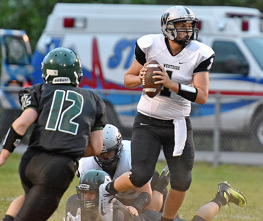 (Brad Davis/The Register-Herald) Westside quarterback Travis Cook looks for an open receiver as he dodges Wyoming East defenders Friday night in New Richmond.