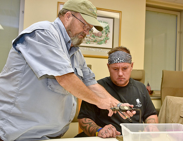 (Brad Davis/The Register-Herald) Healing Waters Program Director Al Cox, left, helping veteran chris Wyatt during a fly making session October 13 at the V.A. Medical Center.