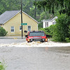 (Brad Davis/The Register-Herald) A driver braves the flood waters, and would make it across,  Monday afternoon in Minden.