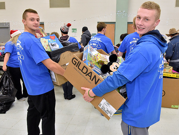 (Brad Davis/The Register-Herald) Volunteers Evan Preece, left, and McQuade Canada notice the camera during the Wyoming County Toy Fund Sunday morning at Wyoming East High School.