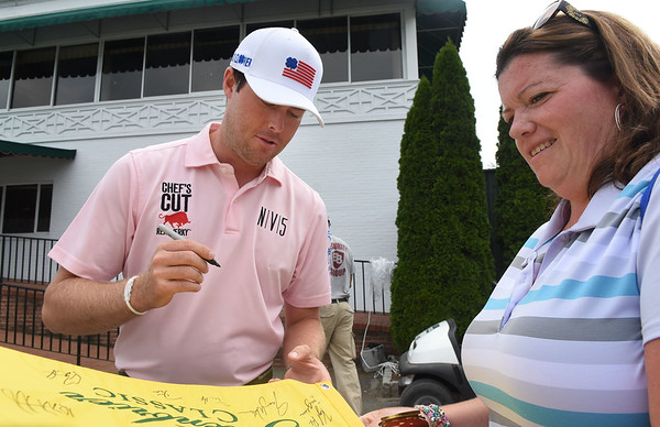 Kyle Reifers, golf pro left, signs an autograph for, Mariah Miller, of Canton Ohio, during the all day Youth Day at The Greenbrier Classic. <br /> (Rick Barbero/The Register-Herald)