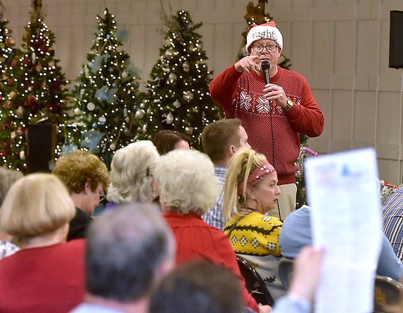 (Brad Davis/The Register-Herald) Auctioneer and emcee Scott Hill points out a bidder in the foreground as customers compete for the Christmas tree they want during the United Way of Southern West Virginia's annual Wonderland of Tree charity event Friday night inside the Crossroads' Mall.