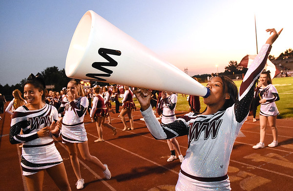 Aiyana Henry,  cheerleader for Woodrow Wilson, left, gets the crowd into the game against Bluefield Friday night at Van Meter Stadium in Beckley.<br /> (Rick Barbero/The Register-Herald)
