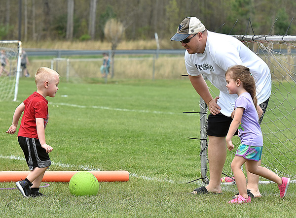 (Brad Davis/The Register-Herald) 4-year-old Brody Jarrell, left, tries to score on dad Brian and twin sister Sophia (the third of the triplets, Amelia, is unphotographed but playing also) as they play a little pick up soccer during a YMCA Healthy Kids Day event Saturday afternoon at the YMCA Paul Cline Memorial Sports Complex.