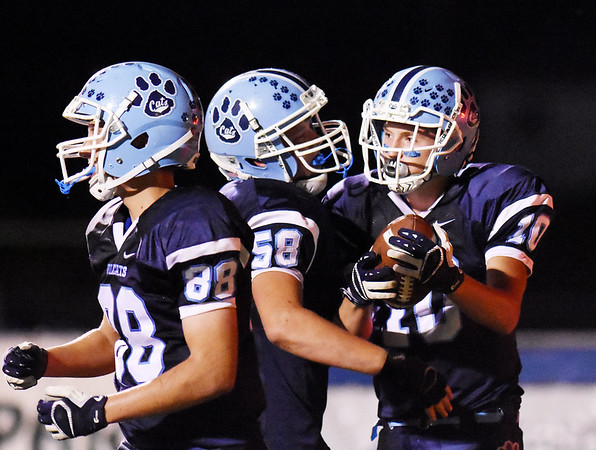 Meadow Bridge's Jared Gladwell (10) is congratulated by Darrelle Burdette (58) and Kobe Rozell (88) after catching their first touchdown during their game against Webster County Friday in Meadow Bridge. (Chris Jackson/The Register-Herald)
