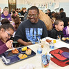 (Brad Davis/The Register-Herald) Steven Cooper, 2nd from left, enjoys some time with his 9-year-old daughter Alysa Eagle (far left), a 4th grader, and 7-year-old son Dasuanta Cooper (right of Steven), a 2nd grader, during a special Soul Food Luncheon Friday morning at Stratton Elementary School. Parents and guardians were invited to visit and sit down for a hot meal and some quality time with their hard-working kids and to check out all the students' special Black History Month projects, which hung on display through the cafeteria.