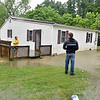 (Brad Davis/The Register-Herald) Scarbro Loop Road resident Nicholas Clark, right, checks on neighbor Amy Jackson as flooding persists after heavy rains in the area Monday afternoon. Despite being surrounded by it the water hadn't made its way into the upper portion of Jackson's home at the time the photo was taken.