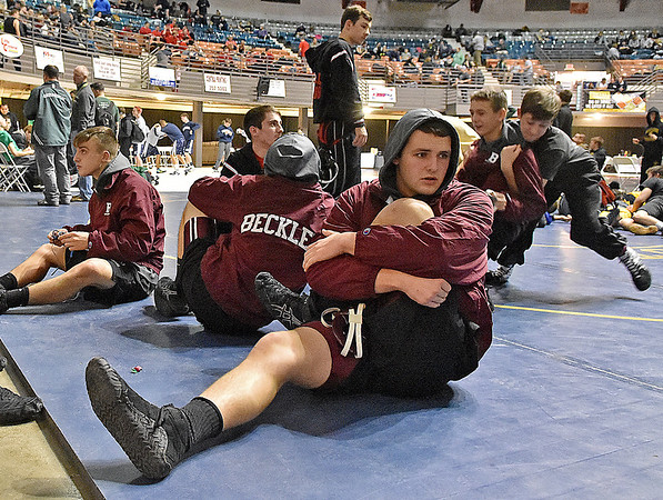(Brad Davis/The Register-Herald) Woodrow Wilson wrestler Caleb Persinger begins his pre-match stretches as he and his Flying Eagle teammates warm up prior to the start of the 36-team West Virginia National Guard Duals Friday afternoon at the Beckley-Raleigh County Convention Center.