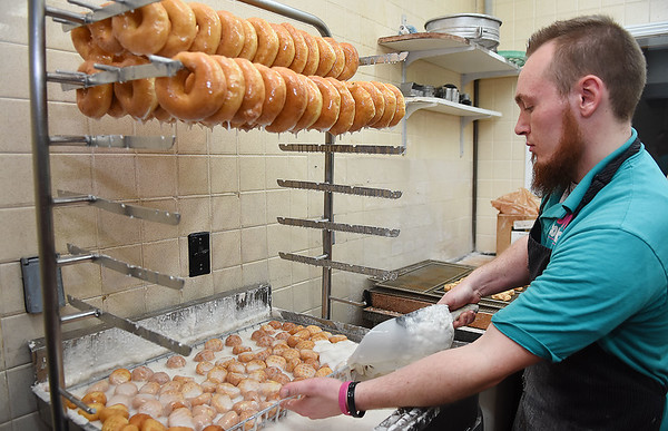 Paul Plumley glazing donuts at the Donut Connection.<br /> (Rick Barbero/The Register-Herald