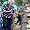 (Brad Davis/The Register-Herald) Lewisburg resident Andrea Morrison reacts as she comes across Dakota Stone's name on the Old Mill Park Memorial following its dedication Firday afternoon in White Sulphur Springs. Her husband Terry follows behind. Stone was a good friend of Andrea and Terry's son Max and they knew him well.