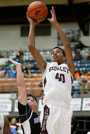 (Brad Davis/The Register-Herald) Woodrow Wilson's Michael Beasley scores as Riverside's Mark Scites defends during the Flying Eagles' win over the Warriors Wednesday night at the Beckley-Raleigh County Convention Center.