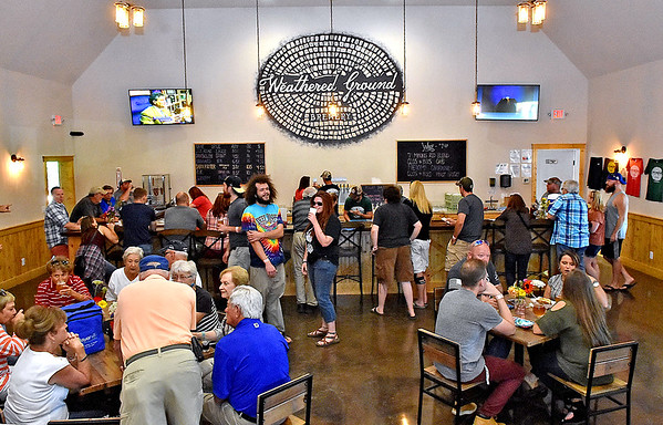 (Brad Davis/The Register-Herald) Patrons hang out in the main pub area during the grand opening celebration for the Weathered Ground Brewery Saturday afternoon in Cool Ridge.