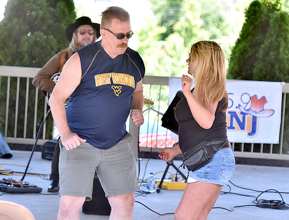 (Brad Davis/The Register-Herald) Montgomery resident Tammy Dunn and Wilkesboro, North Carolina resident David Pearson dance under the Jim Word Park gazebo as country music singer Billy Payne (background) performs during Fridays in the Park yesterday afternoon.