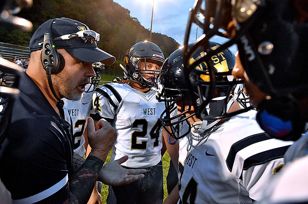 (Brad Davis/The Register-Herald) Greenbrier West players and assistant coach Steve Tincher talk a little last minute strategy prior to the kickoff of their game at Summers County Friday night in Hinton.