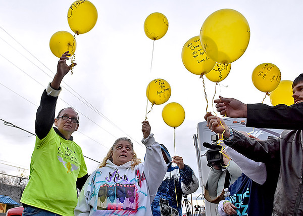 (Brad Davis/The Register-Herald) Mother Leisa Wellington, 2nd from left, joins friends and family as they release balloons into the air with messages of love and hope for son Chaz Richardson, who has been missing since December 3rd of 2015 during a vigil and continued awareness gathering Wednesday evening in Glen Daniel next to the Whitesville State Bank.