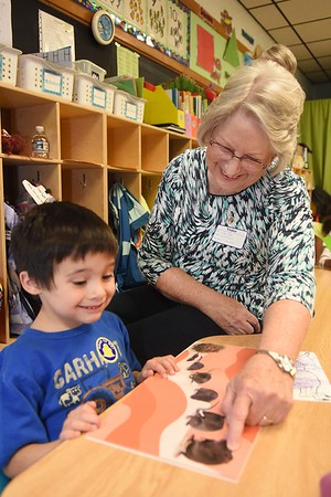 Linda Cole, co-president Fayette Co. chapter Read Aloud West Virginia, helps Darrell Adkins, pre-k student in Andrea Martin's class, read his book he picked out during the Snuggle & Read program held at Mount Hope Elementary School Wednesday morning.<br /> (Rick Barbero/The Register-Herald)