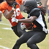 (Brad Davis/The Register-Herald) West (black jerseys) receiver Kenzel Doe returns a kick as East (orange jerseys) defensive lineman Patrick McNeil pursues him during the opening game of The Spring League Saturday afternoon in White Sulphur Springs.