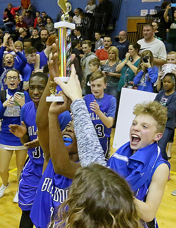 (Brad Davis/The Register-Herald) Beckley-Stratton Middle School players swoop in to collect their trophy after defeating Shady Spring in the Raleigh County Championship game Thursday night in Shady Spring.
