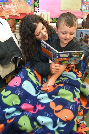 Ashlei Wiseman wraps up in a blanket with her son Trey Donelly reading his My First ABC book in Andrea Martin's pre-k class during the Snuggle & Read program held at Mount Hope Elementary School Wednesday morning.<br /> (Rick Barbero/The Register-Herald)