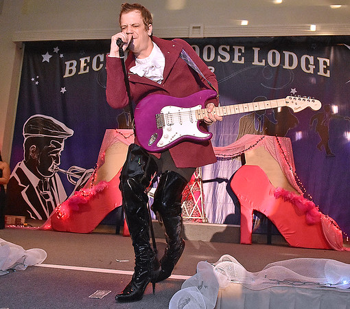 (Brad Davis/The Register-Herald) Participant Jason Lockart rocks out lip-sync style during individual introductions at the annual Hunks in Heels fundraising event for the Women's Resource Center Friday night at the Beckley Moose Lodge.