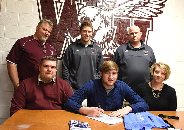 Ellis Lilly, of Woodrow Wilson, front row second from left, signed to play football with Glenville State College. Pictured with Lilly front row from left are his parents, William and Rebeka Lilly, back row from left, assistant coaches Dale Stafford, Ryan Stafford and head coach Street Sarrett. <br /> (Rick Barbero/The Register-Herald