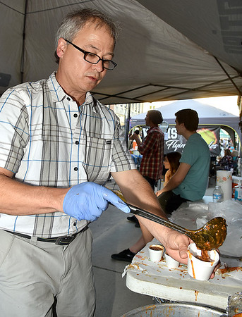 (Brad Davis/The Register-Herald) Elevation Sports owner Mark Hitchcock keeps chili cups flowing at their booth during Beckley's annual Chili Night event Saturday evening.