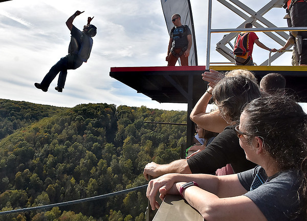 (Brad Davis/The Register-Herald) A B.A.S.E. jumper points to the sky as he leaps over the edge during Bridge Day Saturday afternoon.