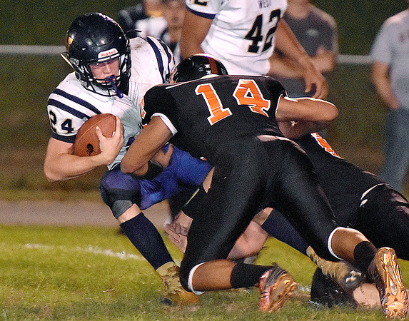 (Brad Davis/The Register-Herald) Greenbrier West's Chase Patterson is taken down by Summers County's Christian Pack (#14) and Tucker Bennett Friday night in Hinton.