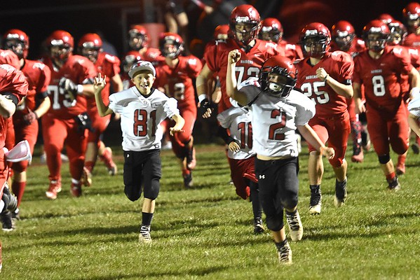 Couple youths run out on the field with the Liberty Raiders football team before the game againt Independence Friday night at Liberty High School.<br /> (Rick Barbero/The Register-Herald)