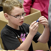 (Brad Davis/The Register-Herald) Seven-year-old Connor Reed checks out a tiny toy item during the annual Mac's Toy Fund event Saturday morning at the Beckley-Raleigh County Convention Center.