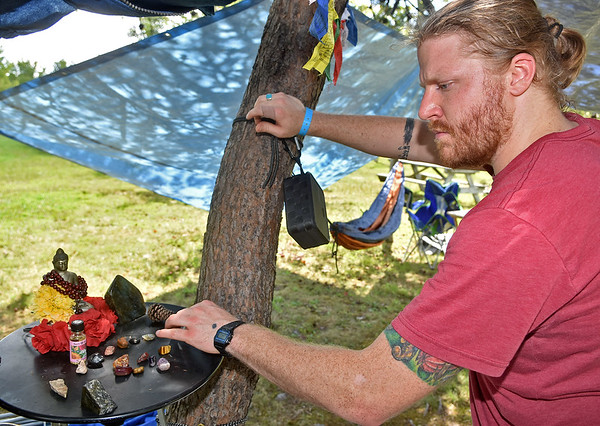 (Brad Davis/The Register-Herald) Charleston resident Joel Eary sets up a nice meditation area, complete with a small Buddha, for himself and friends that came with during the opening hours of the Cluster Music & Arts Festival going on this weekend at Ace Adventure Resort Thursday afternoon in Minden. It's only the 2nd annual event, which was held in Flatwoods last year, and it'll be running through Sunday afternoon. It's a smaller event than the annual Mountain Music Festival but comes with a similar crowd and vibe.