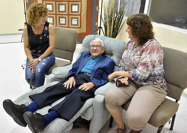 (Brad Davis/The Register-Herald) Harlan Mann, turning 100 years old next week, relaxes in his own designated recliner with granddaughter Kristin Vandall at left and grandniece Penny Foreman during the opening moments of an early birthday party for him thrown by family at Beckley Regular Baptist Church Saturday evening.