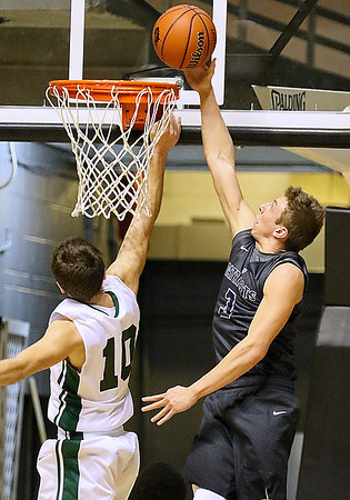 (Brad Davis/The Register-Herald) Independence's Tyler Haga tries to dunk home an offensive board as Wyoming East's Logan Mullins defends during Big Atlantic Classic action Wednesday night at the Beckley-Raleigh County Convention Center.