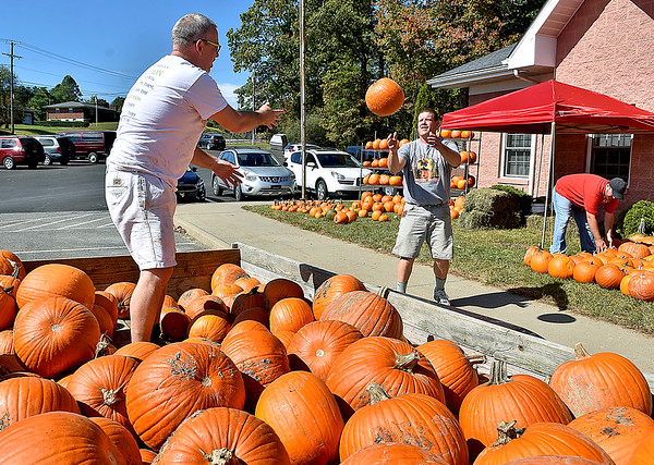 (Brad Davis/The Register-Herald) Volunteer Mark Allen, left, tosses pumpkins to fellow volunteer Jim Givens Thursday afternoon, who then hands them to Josh Thomas, who puts them into place as the three prepare the Beckley campus for Burlington United Methodist Family Service's annual Pumpkin Festival coming up this weekend.