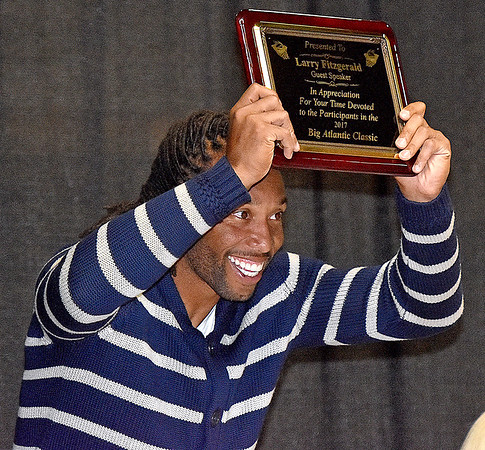 (Brad Davis/The Register-Herald) Arizona Cardinals receiver Larry Fitzgerald proudly waves his newly earned plaque as he thanks the crowd following a speech as the keynote speaker of the Big Atlantic Classic Tip-Off Banquet Sunday afternoon at the Beckley-Raleigh County Convention Center.