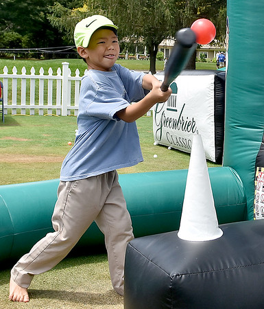(Brad Davis/The Register-Herald) Seven-year-old Anand Edgar is less interested in the golf than he is crushing the ball at a special air teed, inflatable batting cage inside the kids zone Saturday in White Sulphur Springs.