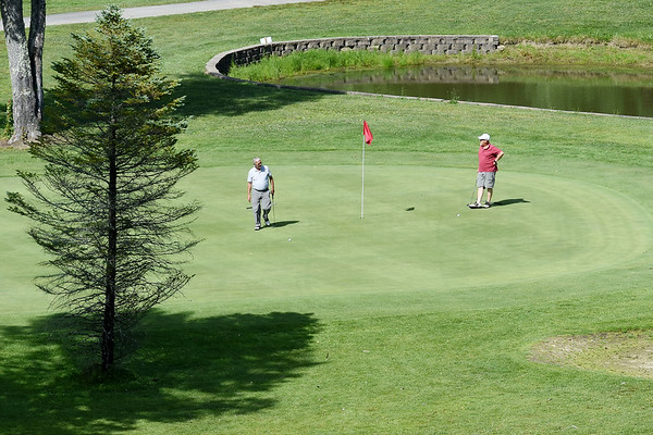 Two men test their game on the No. 15 hole at The Briar Patch Monday. Are temperatures were near perfect and should not see rain clouds until late in the week. (Chris Jackson/The Register-Herald)