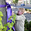 (Brad Davis/The Register-Herald) Women's Resource Center volunteer Tanner Pace ties a purple ribbon to a tree around town for domestic violence awareness month Sunday afternoon in uptown Beckley. Bessie's Floral Designs in Oak Hill and Flowers by Nancy in Beckley donated the ribbons and materials to the Women's Resource Center.