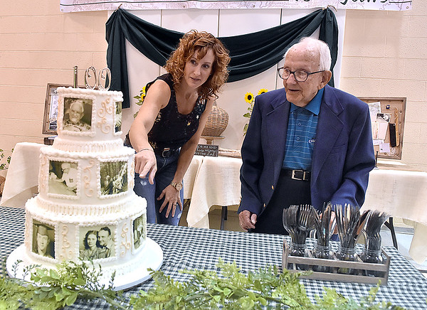 (Brad Davis/The Register-Herald) Harlan Mann, turning 100 years old next week, marvels at a special cake made for him that includes several photos, all edible, from different periods in his life during an early birthday party for him thrown by family at Beckley regular Baptist Church Saturday evening.