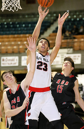 (Brad Davis/The Register-Herald) Oak Hill's Tyrese Selinger drives and scores as Ambassador Christian's Chandler Fluty, left, and Isaac Moore defend Friday night at the Beckley-Raleigh County Convention Center.