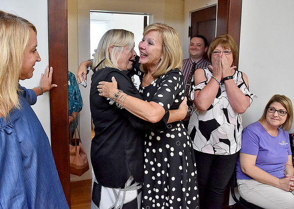 (Brad Davis/The Register-Herald) Outgoing United Way of Southern West Virginia executive director Magaret Ann O'Neal, middle, gets a big from friend Marcy Nolan during a special sendoff celebration for her at the organization's Croft Street location Friday afternoon.
