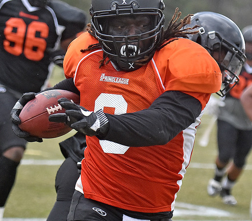 (Brad Davis/The Register-Herald) East (orange jerseys) running back Anthony Dixon rumbles ahead against West (black jerseys) during the opening game of The Spring League Saturday afternoon in White Sulphur Springs.