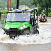 (Brad Davis/The Register-Herald) Minden residents use ATV's to cross flood waters at the intersections of Minden Road and McKinney Road Monday afternoon.