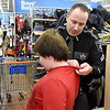 (Brad Davis/The Register-Herald) Raleigh County Sheriff's Deputy H.W. Long, II checks the t-shirt size of nine-year-old Kyle Farris before shopping for new clothes together during a special Shop With a Deputy event Sunday afternoon at the MacArthur Walmart. Several Raleigh County Sheriff's Deputies and West Virginia State Troopers spent the day taking kids around the store with $100 budgets to spend on whatever they chose.
