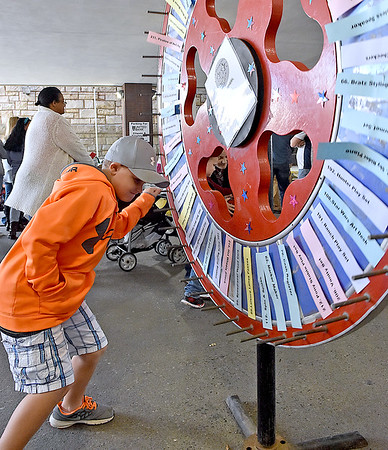 (Brad Davis/The Register-Herald) Chance Moore winds up and takes a chance with a spin on the massive prize wheel inside the arcade under United Bank during the Kids Classic Festival Saturday morning.