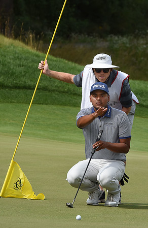Sabastian Munoz looks over his birdie putt on the 12th hole with his caddy Danny Rennerson during the third round of The Greenbrier Classic.<br /> (Rick Barbero/The Register-Herald)