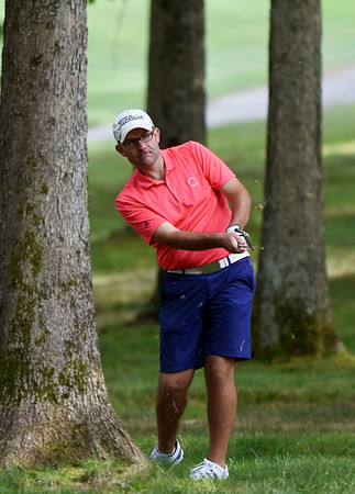 Aaron Kemlock hits out of the trees on the No. 12 hole during the championship round of the annual BNI Tournament Monday at The Resort at Glade Springs. (Chris Jackson/The Register-Herald)