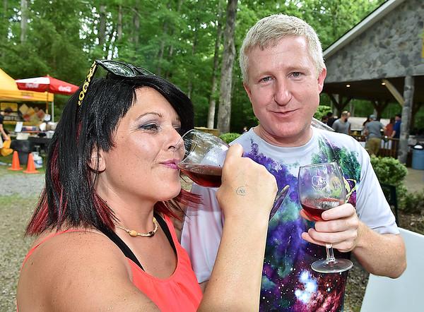 (Brad Davis/The Register-Herald) Beckley resident Karen Lilly and Hurricane resident Stu Frazier enjoy some wine and summer weather during Daniel Vineyards' Spring Wine Fest Saturday.