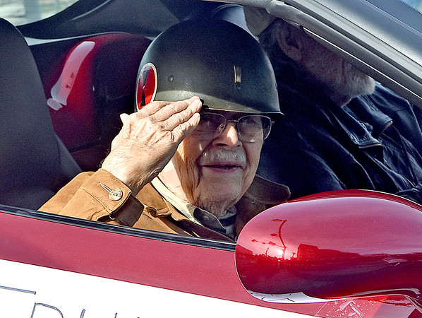 (Brad Davis/The Register-Herald) World War II veteran Truman Sayre salutes the crowd that salutes him and other veterans as they ride along during the annual Veterans Day Parade Saturday morning.