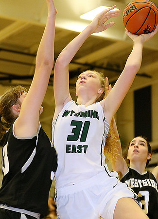 (Brad Davis/The Register-Herald) Wyoming East's Emily Saunders drives to the basket as Westside's Morgan Thomas defends Wednesday night in Clear Fork.